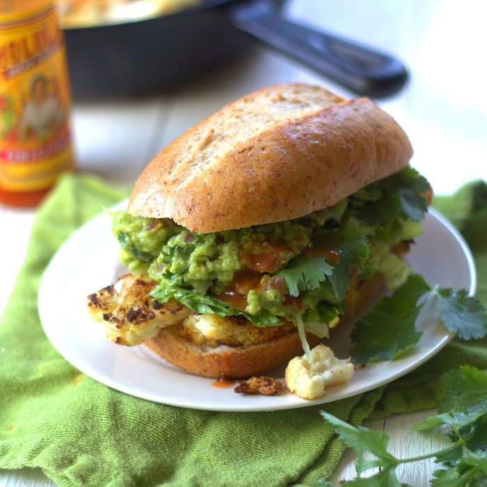 Slabs of cauliflower are pan seared and roasted with spices before being stuffed into sandwich rolls with guacamole in these Mexican inspired sandwiches.