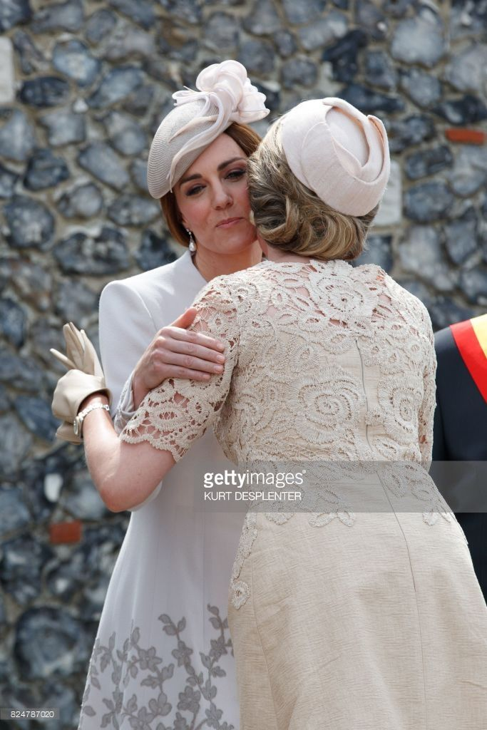 Britain's Princess Kate, the Duchess of Cambridge (L) embraces Queen Mathilde of Belgium during the commemorations at The Tyne Cot Commonwealth War Graves Cemetery in Zonnebeke on July 31, 2017, as part of a series of commemorations for the 100th anniversary of the Battle of Passchendaele. The battle of Passchendaele, also called the third battle of Ypres, took place between July 31 and November 6, 1917 in Passendale, West Flanders. / AFP PHOTO / BELGA AND Belga / KURT DESPLENTER / Belgium…