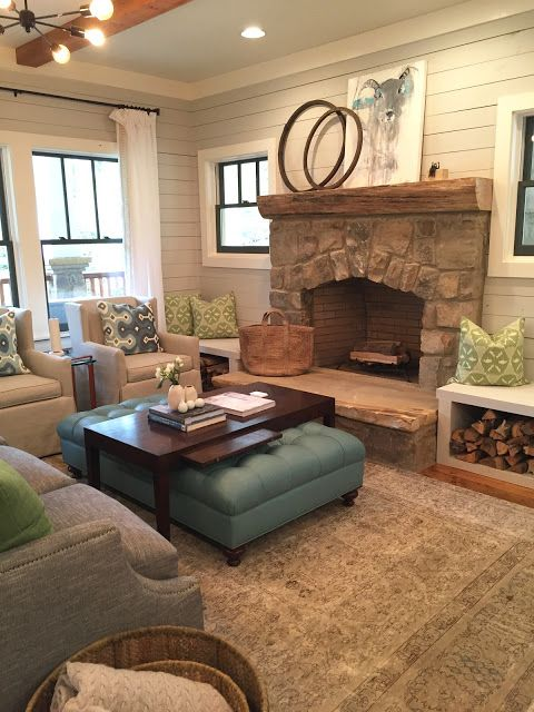 Bench for firewood  gray shiplap walls, black windows, stone fireplace with bench on side