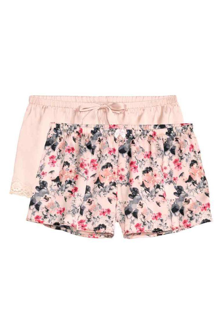 Pantaloni scurţi, 2 perechi: Pantaloni scurţi de pijama, din satin, cu elastic în talie. O pereche sunt cu imprimeu, cealaltă uni, cu garnituri din dantelă la tiv.