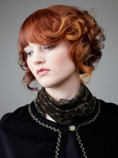 Straight bangs to a curled out fringe is one creative take on a medieval avant-garde hairstyle. To accentuate this cut the coloring is on point going from a red to one side gradually to a beautiful reddish orange on the fringe.