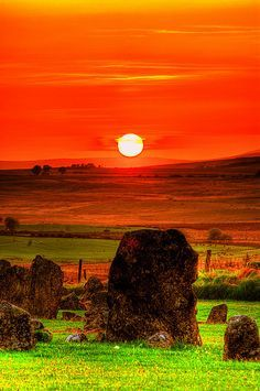 """Sunset over Beaghmore Stone Circles, Ireland, a complex of early Bronze Age megalithic features, stone circles and cairns, near Cookstown, Co.Tyrone, N.Ireland on the edge of the Sperrin Mountains. Documents suggest that Beaghmore translates as 'the moor of the birches' but Mackay's Dictionary of Ulster Place-names says that it is from an Bheitheach Mhór meaning """"big place of birch trees""""; a name that reflects the fact that the area was a woodland before being cleared by Neolithic farmers"""