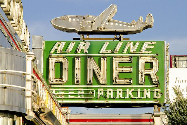 What a great sign. It looks like the plane is going to land on the diner's roof.