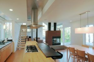 A brick-and-glass framed fireplace seats aplomb at the center of this angular minimalist transition kitchen. Photo by Gossens Bachman Architects