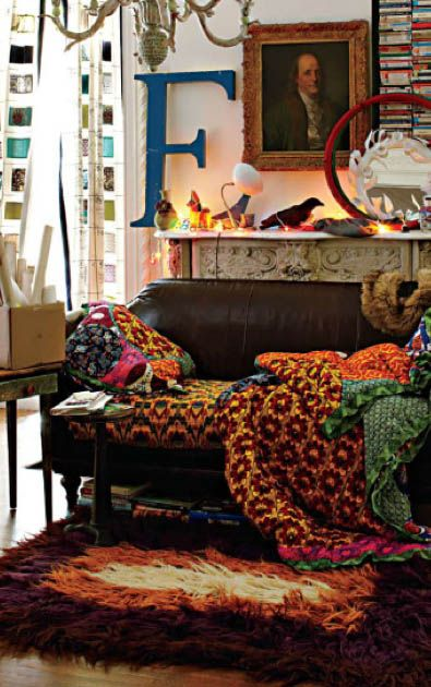 Eclectic design at its best.  This small living room packs a punch of different colors & patterns, uses large & small scale accents but it works because the white walls & the solid leather sofa act as an anchor to all the colorful mix-matched accents. For a second I thought the blanket was a giant peacock blanket.