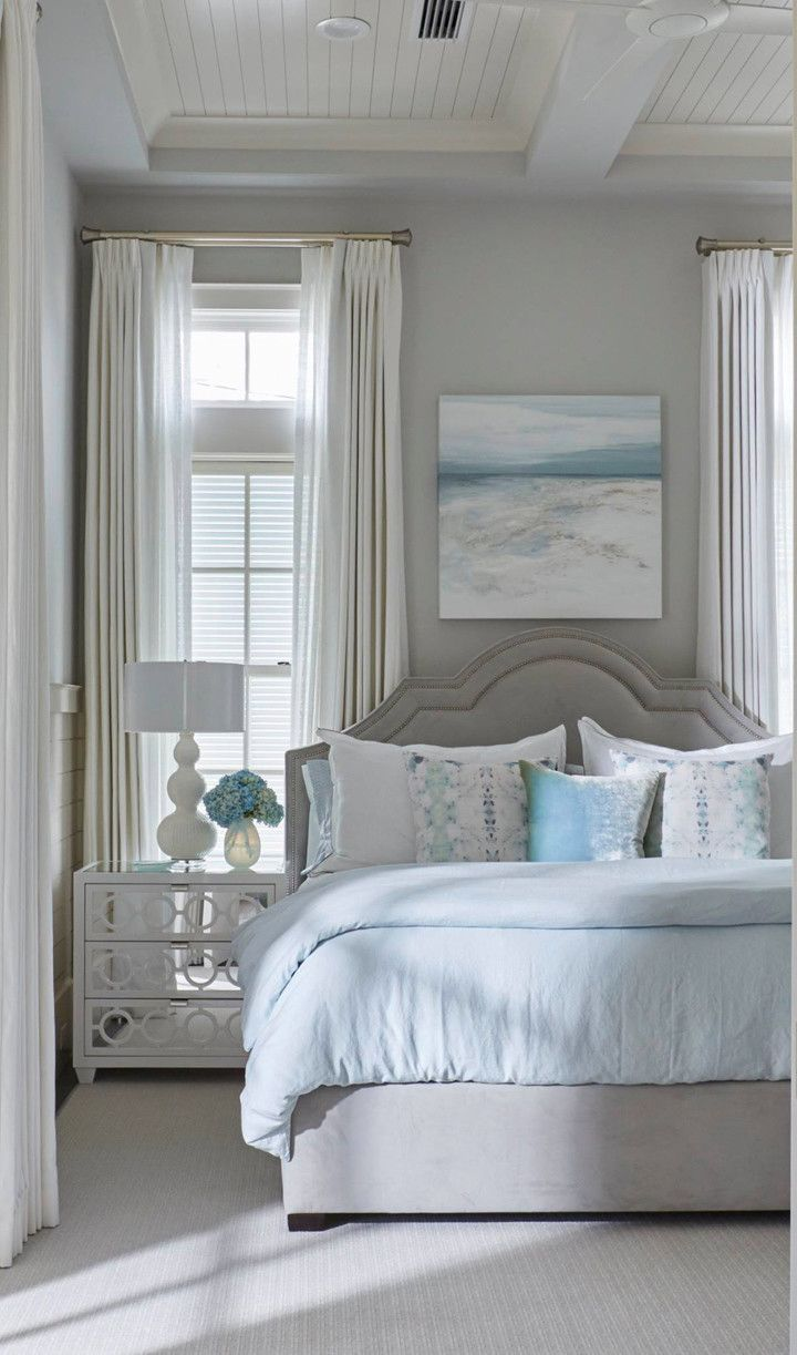 Blue and white bedroom - This Blue And Gray Guest Bedroom Features A Gray Velvet Bed Dressed In White And Pale Blue Bedding Placed Next To A White Mirrored Nightstand