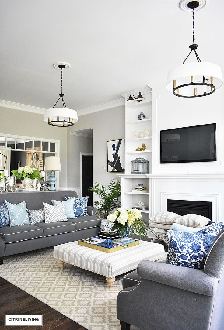 Elegant, open concept living room, with with grey sofas and drum shade pendant lights create a neutral backdrop of layers of beautiful blue patterned pillows and blue and white pottery. Decorated for Summer with fresh cut greenery, hydrangeas and palms.