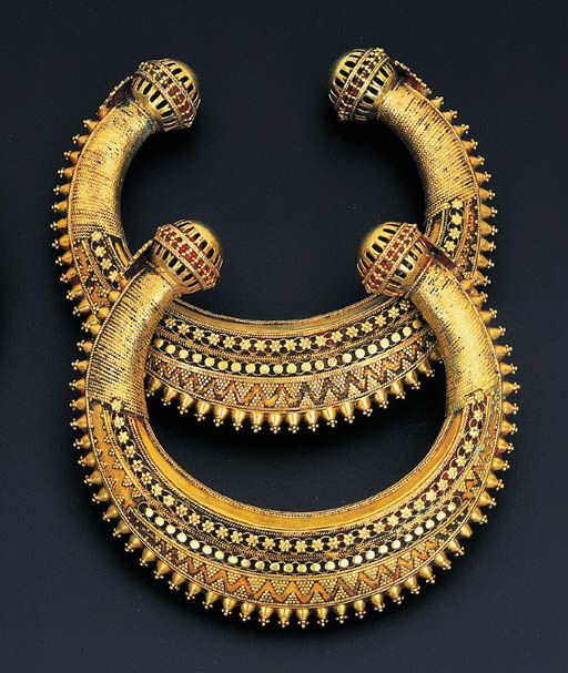 A PAIR OF SOUTH INDIAN KADAS Each torque bangle decorated with applied beaded and foliate motifs to the openwork spherical terminals, late 19th century.