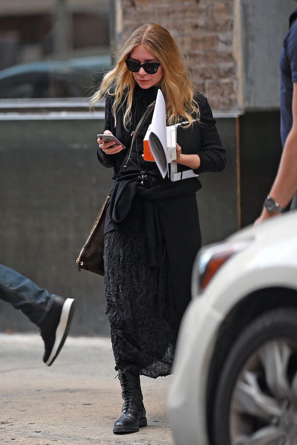 Ashley Olsen was recently spotted in New York City in an all black edgy chic look. She wore cat-eye sunglasses, a cardigan, sheer textured dress, a sweater tied at the waist and leather combat boots.