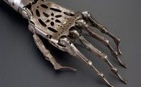 """Made from steel and brass, the elbow joint on this artificial arm can be moved by releasing a spring, the top joint of the wrist rotates and moves up & down, and the fingers can curl up and straighten out. The wearer may have disguised it with a glove. Among the most common causes of amputation throughout the 1800s were injuries received as a result of warfare.""  - Science Museum"