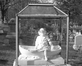 The children under glass are life sized white marble statues of the children buried there. (It is said that some of the statues of children in the cemeteries were made from their death masks. A common practice in the Victorian period.) A boy in a boat with his toys and a girl standing with flowers in her hand. They were their mother's only children and their mothers are now buried next to them.