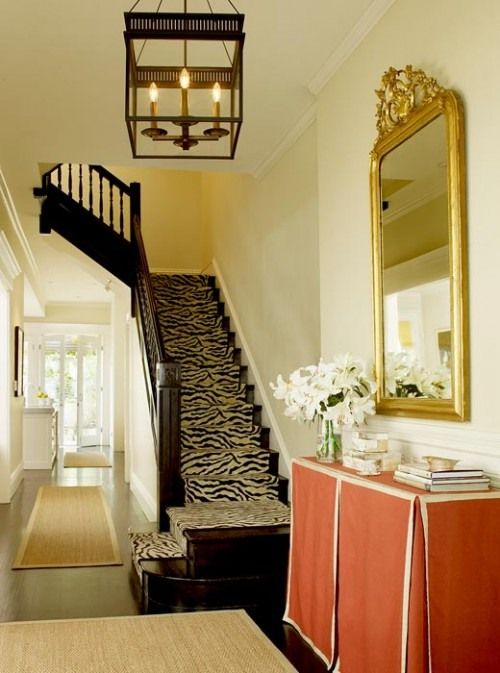 palmer weiss entry with orange skirted table and zebra stair runner via awid