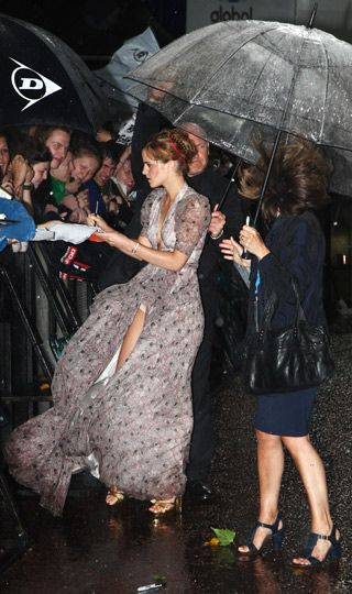 Emma Watson braved heavy rain and mischievous winds to walk the red carpet in a…