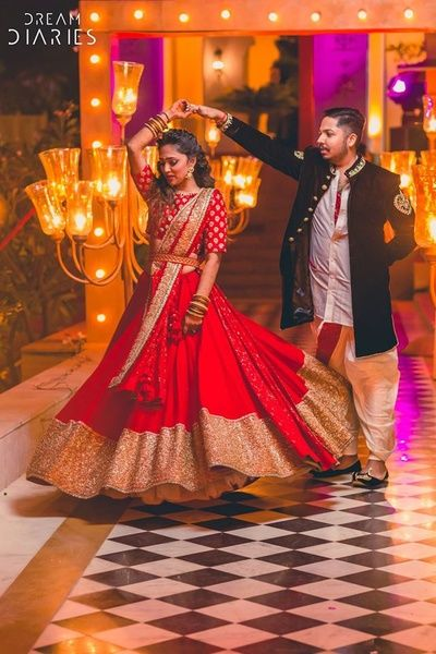 Candid Couple Shots - Twirling Bride in a Red Lehenga with Gold Sequin Border and Belted Dupatta and the Groom in Dhoti Pants and Black Jacket | WedMeGood #indianbride #indianwedding #wedmegood #twirlingbride #brideandgroom #coupleshot #candid #lehenga #bridal
