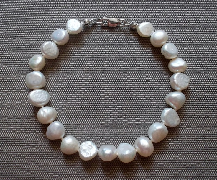 Individually knotted 8-9mm white/cream baroque shape freshwater pearl bracelet. 8 inches in length, with a sterling silver clasp.