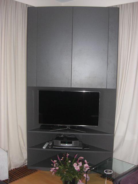 Op maat gemaakt audio meubel in een hoek. Achter de kast is plaats om de gordijnen weg te schuiven.