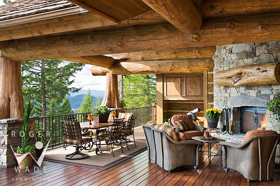 roger wade studio architectural photography of covered deck and fireplace looking out to mountain view, luxury handcrafted log home, whitefish, montana, by high country builders and the old world cabinet company
