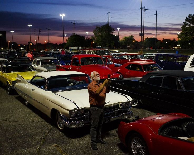 Bruce Greenwood, of Orangeville, Ontario, takes a picture while waiting at the staging area with hundreds of classic cars from all eras before the start of Back to the Bricks 2015 on Saginaw Street in Flint, Mich. on Saturday Aug. 15, 2015. The classic car event held annually on the brick stretch of road in downtown Flint draws thousands of vehicle owners and enthusiasts from across the country.  (Christian Randolph/Flint Journal)