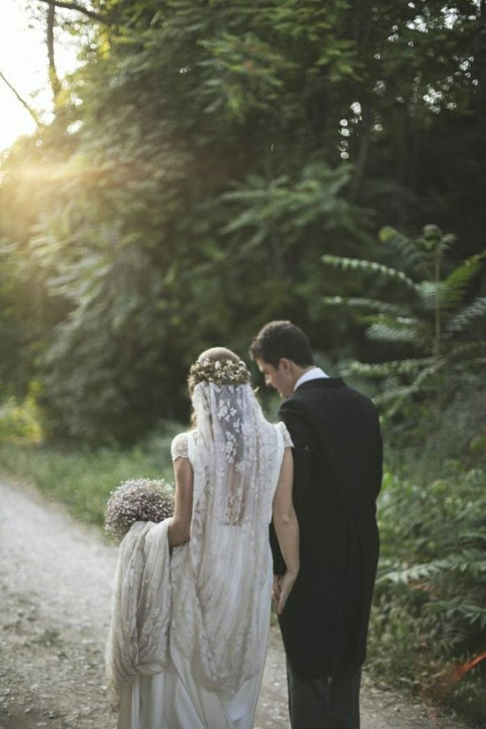 bride wearing long vintage lace dress, flower crown and veil and groom in black suit, both facing backwards, walking on a country road surrounded by trees,