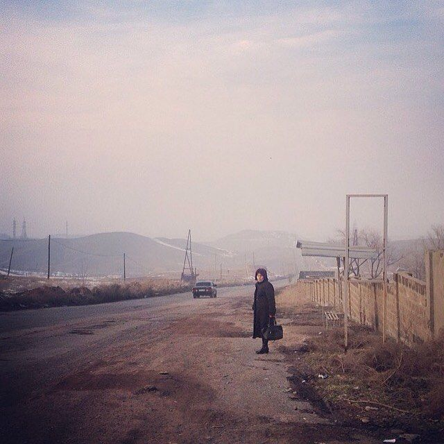 Photo taken by @markosian in Alashkert Armenia |  A woman waits for transport after visiting a cemetery in rural Armenia. by natgeo