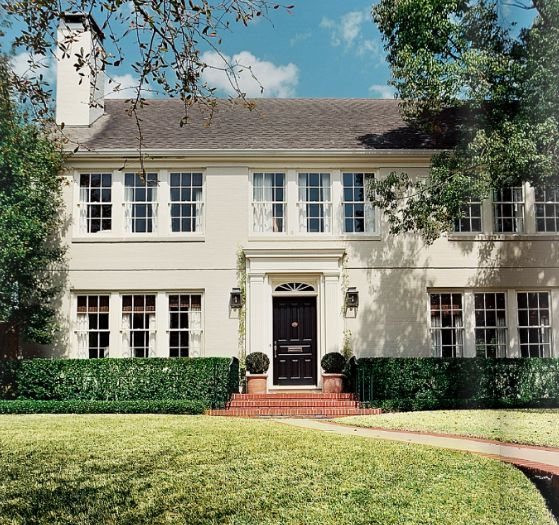 Traditional painted brick lots of windows glossy black for Stucco and brick homes