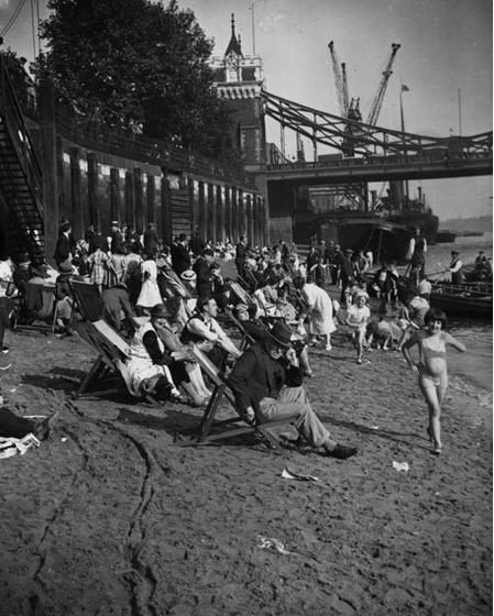 1935: Bathers enjoy a beach on the Embankment by Tower Bridge.