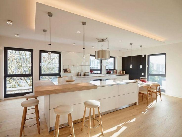Meubles blanc et bois clair et plancher assorti dans la cuisine avec îlot central, bar et tabourets hauts