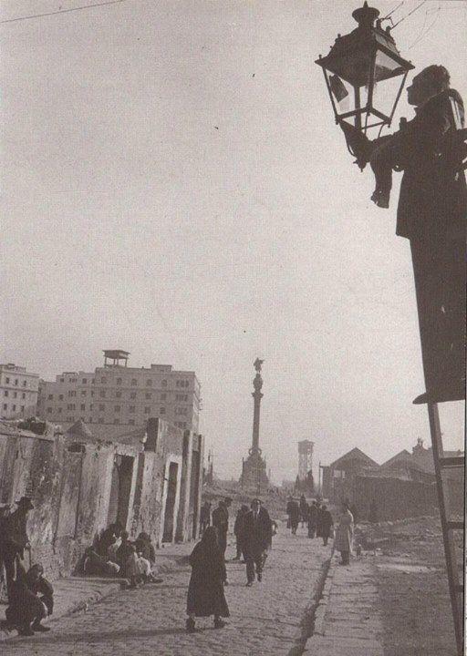 Un farolero subido a la escalera para encender el alumbrado de las calles del Raval. Años 50.