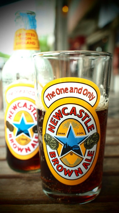 Newcastle Brown Ale. Originally brewed in Newcastle Upon Tyne, England, it is now brewed in Tadcaster, North Yorkshire. In England, it has always been thought of as a blue-collar, working man's beer, but in America, it has become a rather trendy import. I am quite fond of it, myself. It is very well-balanced and always a solid choice, as it pairs well with many different foods.