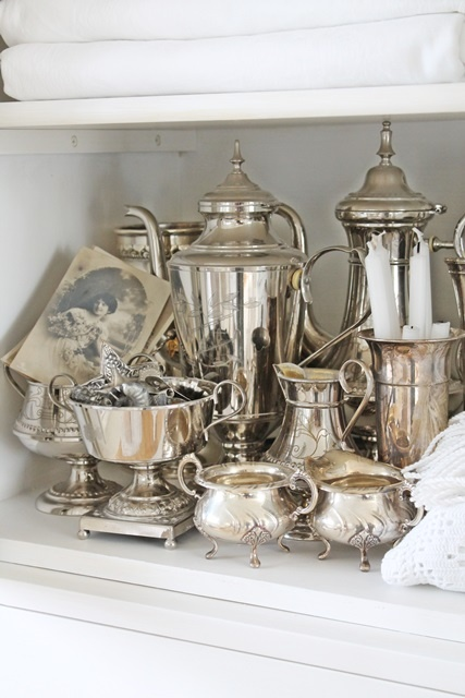 Vintage silver collection arranged on shelf.