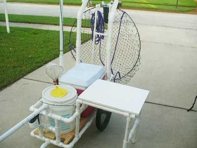 pvc homemade fishing cart with table folded out from cart, big hoop net on the back, cooler, bait bucket