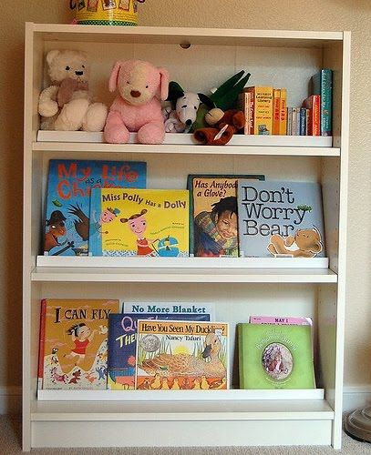 Turn a bookcase into a front facing book display - repurpose Billy bookcases with a few strips of moulding.