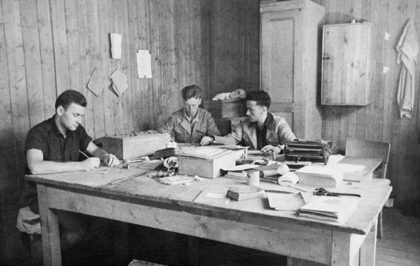 Three British prisoners of war produce news sheets in one of the huts at Stalag Luft III PoW camp.