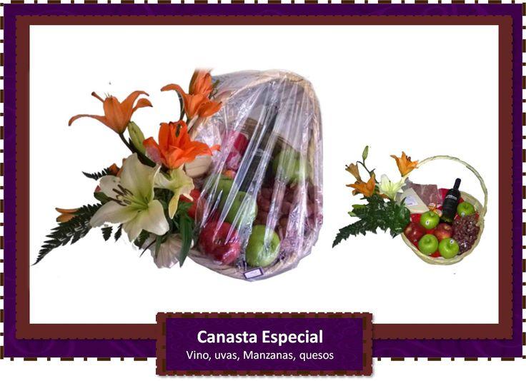 Canasta de vino con frutas, quesos y proscuito decorada con flores sobre canasta tejida