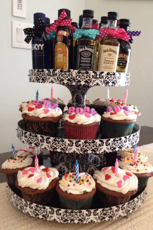 21st birthday cupcake tower - small bottles of liquor tied with ribbon make up the top of the tower!