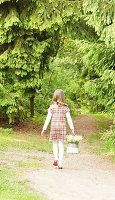 Kleines Mädchen mit Maiglöckchen im Korb auf Waldweg
