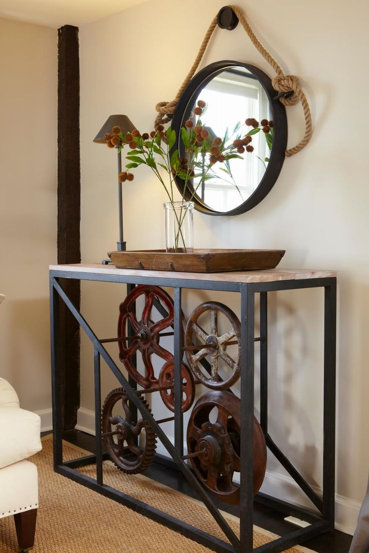 An industrial style table is paired with a rope hung mirror and rustic wood t