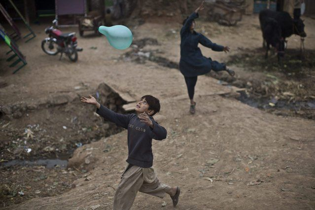 Juegos para Niños Alrededor del Mundo Un niño refugiado afgano persigue un globo mientras jugaba en un barrio pobre en las afueras de Islamabad, Pakistán, el domingo 2 de febrero de 2014. (Foto por Muhammed Muheisen / AP Photo)