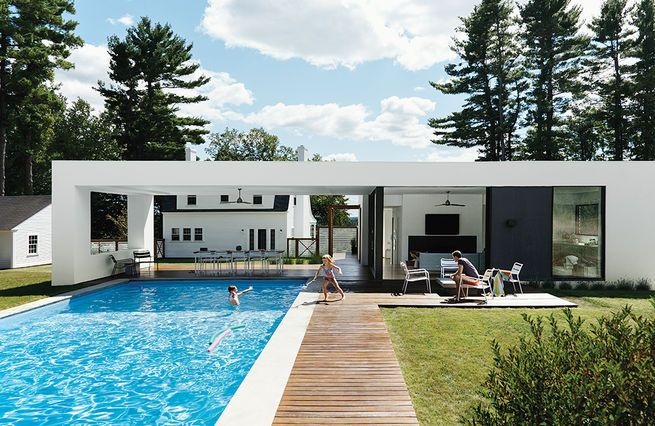 A prefab pool- and guesthouse designed by LABhaus frames views of a Massachusetts property's original structure, a Dillman model Sears, Roebuck kit house from 1928.  Photo by: Tony Luong