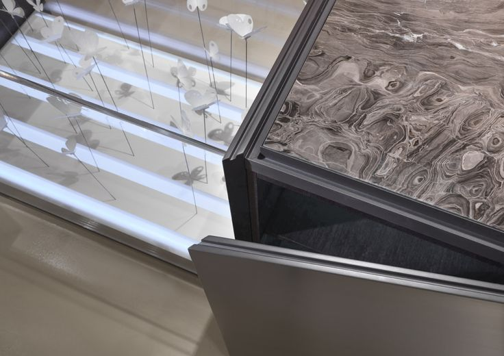 A perimetric groove in lacquered aluminum helps maintaining the vertical surfaces of the doors clean; the doors are 88.5 cm high, with a skirting 6 cm high, for a total height of cm. 94.5. The display cases, monoliths that enhance the working islands, are completely transparent and can be completely opened; made with light bases, they create plays of light and hide some freshners for the fragrance release which have been exclusively designed for Laurameroni by Oikos.