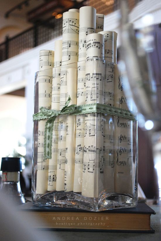 Eclectic glass containers tied with gold ribbon containing rolled sheet music of different heights on top of gold sprayed encyclopedias