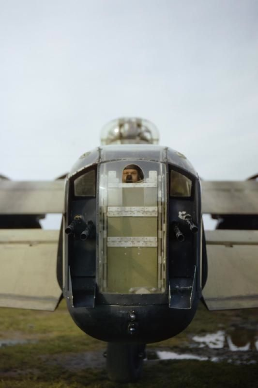 A gunner, believed to be RAF Sergeant J Bell, looks through the opening in the perspex of the rear turret of Avro Lancaster R5740/`KM-O'. The four guns shown are Browning .303 machine guns