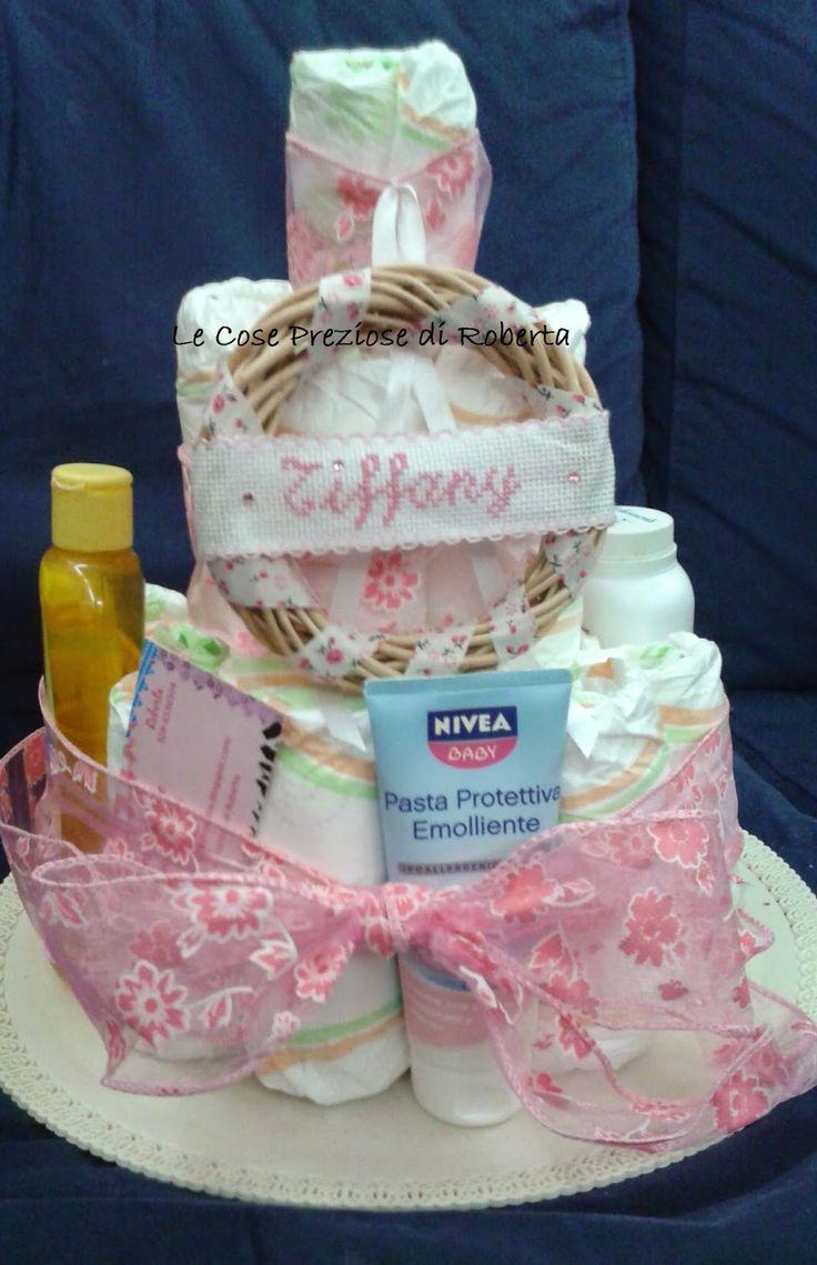 Torta pannolino creata con pannolini, prodotti igiene e coccarda personalizzata con il nome della bambina