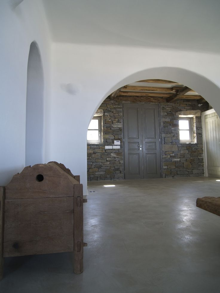 Beton cire floors and white arches in a typical Cycladic living room.