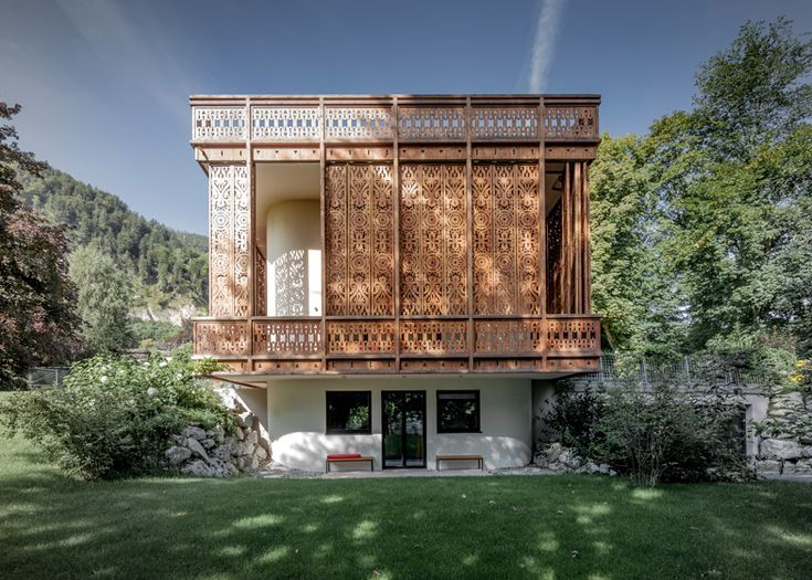 Ornate patterns have been carved into the wooden screens that surround this lakeside villa in western Austria