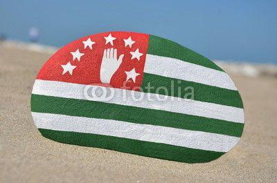 Flag of Abkhazia ( Georgia ) on a stone with beach background