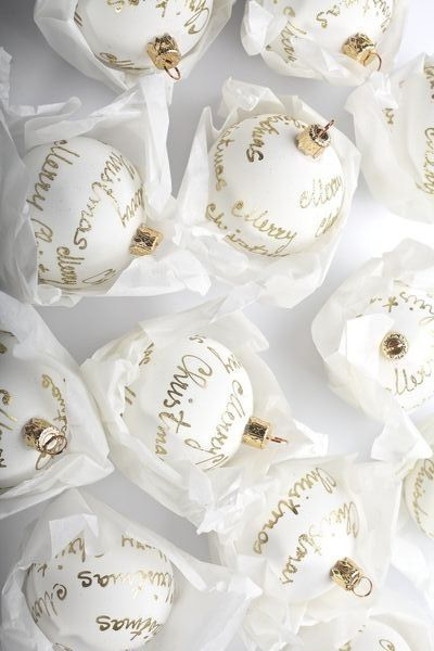Handwritten Words On White Ornaments With A Gold Sharpie.