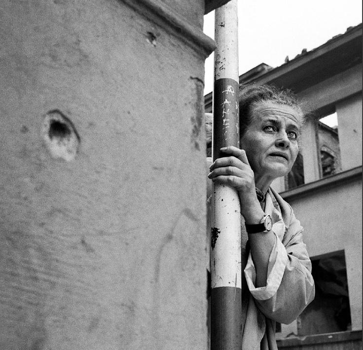 """She is afraid of the snipers in Sarajevo """"Sarajevo, 1993. Une femme rassemble son courage avant de traverser l'avenue principale. Surnommée « Sniper Alley » , celle- ci était sous le feu des tireurs isolés et abritait un des rares points d'eau potable de la capitale."""" Photo Tom Stoddart."""