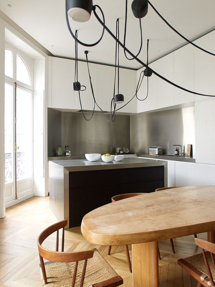 Contemporary Eclectic Kitchen: A contemporary light fixture above a Charlotte Perriand table in a modern kitchen.