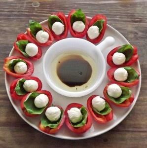 Half uitgehold tomaatje,basilicumblaadje erop en een bolletje mozzarella.